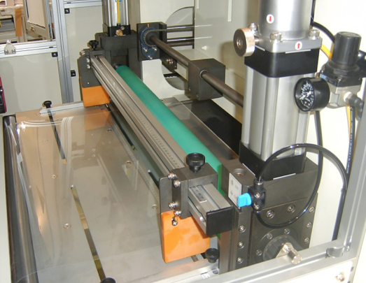 Pinch roll feed system featuring PET belt as the cutting surface with adjustable material edge guides.