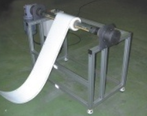 Infeed motorized material roll stand with air-shaft core clamp with lazy loop control minimizes material tension during feeding.  The roll stand is also available without the air-shaft and lazy loop control